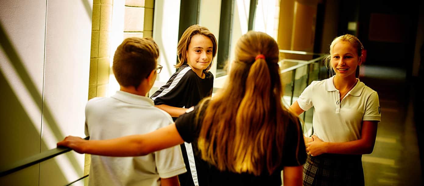 Quatre étudiants et étudiantes du Collège Trinité discutant dans le corridor.